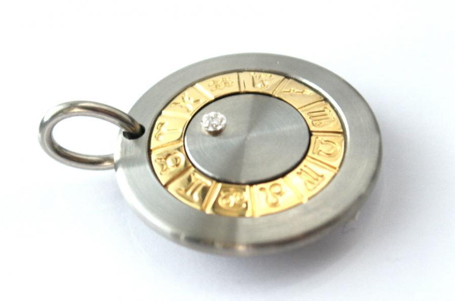 Horoskooppi -riipus, terästä, kultaa ja timantti.